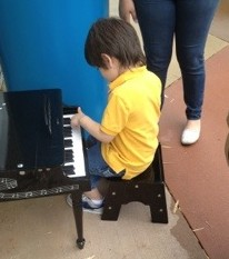 child playing a toy piano