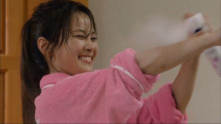 woman smiling while spraying on whitener