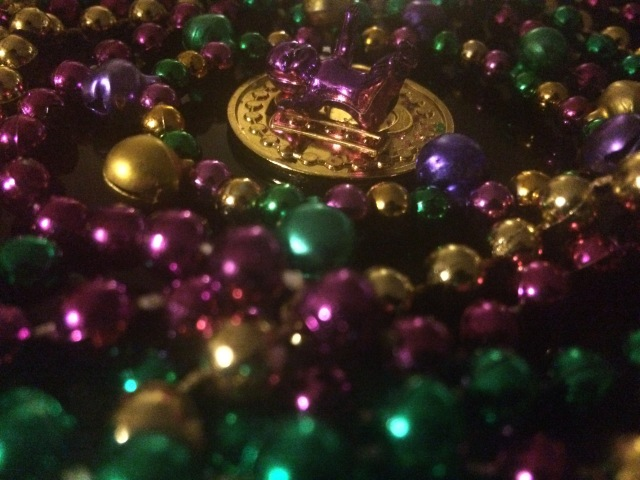 mardi gras beads, coin and king cake baby