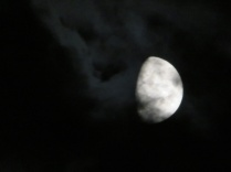 waxing gibbous moon in dark clouds