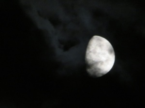 waxing gibbous moon in dark clouds